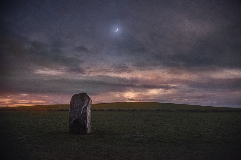 Crescent Moon rising over one of the stones of West Kennet Avenue, Avebury, UK