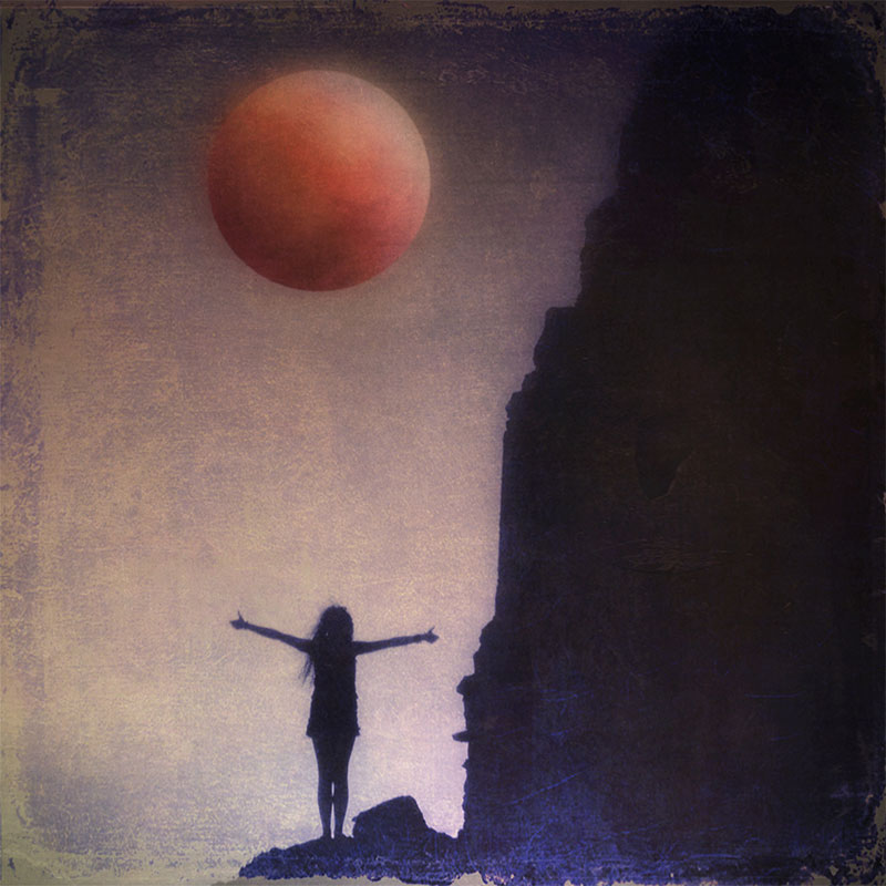 Red Moon rising over a figure, arms outstretched upon a cliff