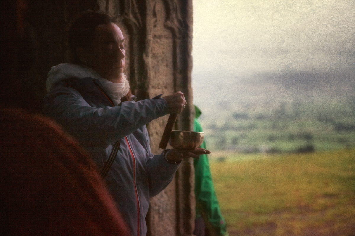 Photo of a woman with a Tibetan prayer bowl atop Glastonbury Tor